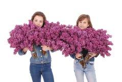 Adolescente de dos muchachas que se coloca con la lila en manos Imagen de archivo libre de regalías