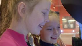 Adolescente de dos muchachas que usa la pantalla interactiva para comprar el boleto en la estación de metro moderna almacen de metraje de vídeo