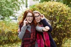 Adolescente de dos novias que camina en el parque y el Hamming para un p Fotos de archivo