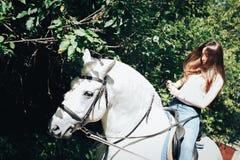 Adolescente de fille et cheval blanc en parc en été Photos libres de droits