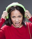 Adolescente de griterío que oscila hacia fuera sostener los auriculares Foto de archivo libre de regalías