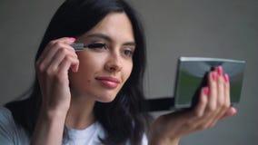 Adolescente de la belleza que aplica maquillaje del rimel y que se admira en el espejo Muchacha hermosa del estudiante que mira e almacen de metraje de vídeo