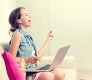 Adolescente de la belleza que se sienta en el sofá en casa y que usa el ordenador portátil Foto de archivo
