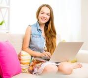 Adolescente de la belleza que se sienta en el sofá, usando el ordenador portátil y la sonrisa Fotografía de archivo libre de regalías