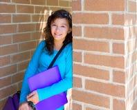 Adolescente de la colegiala en la pared de ladrillo de la escuela feliz Foto de archivo