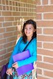 Adolescente de la colegiala en la pared de ladrillo de la escuela feliz Fotografía de archivo