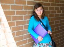 Adolescente de la colegiala en la pared de ladrillo de la escuela feliz Foto de archivo libre de regalías