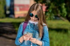 Adolescente de la colegiala de la muchacha Verano en naturaleza Gafas de sol En sus manos sostiene un smartphone El concepto de n Foto de archivo