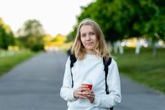 Adolescente de la colegiala de la muchacha Verano en naturaleza En sus manos sostiene el vidrio con café o té caliente Primer que Fotos de archivo