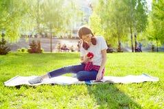 Adolescente de la estudiante que descansa y que lee en libro del parque Imagen de archivo