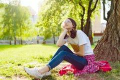 Adolescente de la estudiante que descansa y que lee en libro del parque Imágenes de archivo libres de regalías