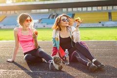 Adolescente de la madre y de la hija que descansa después de entrenamiento en el estadio Foto de archivo libre de regalías
