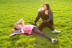 Adolescente de la madre y de la hija que descansa después de entrenamiento en el estadio Imágenes de archivo libres de regalías