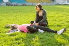 Adolescente de la madre y de la hija que descansa después de entrenamiento en el estadio Fotografía de archivo