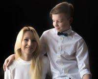 Adolescente de la mamá y del hijo en un fondo negro Imágenes de archivo libres de regalías