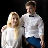 Adolescente de la mamá y del hijo en un fondo negro Fotografía de archivo
