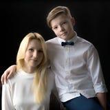 Adolescente de la mamá y del hijo en un fondo negro Foto de archivo