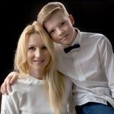 Adolescente de la mamá y del hijo en un fondo negro Foto de archivo libre de regalías