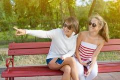 Adolescente de la mamá y de la hija que habla y que ríe mientras que se sienta en el banco en el parque Fotos de archivo