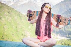 Adolescente de la moda con el monopatín del longboard en la montaña Fotos de archivo