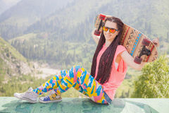 Adolescente de la moda con el monopatín del longboard en la montaña Imagen de archivo libre de regalías