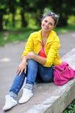 Adolescente de la moda de los jóvenes que sonríe en un parque Imágenes de archivo libres de regalías