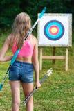 Adolescente de la muchacha con el arco y las flechas delante de la blanco Fotografía de archivo libre de regalías