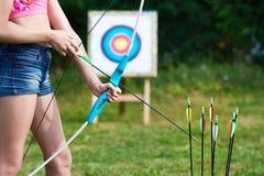 Adolescente de la muchacha con el arco y las flechas en el fondo de la blanco Foto de archivo