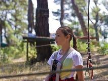 Adolescente de la muchacha con el equipo que sube en un parque de atracciones de la cuerda Imagen de archivo