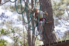Adolescente de la muchacha con el equipo que sube en un parque de atracciones de la cuerda Fotografía de archivo libre de regalías