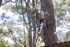 Adolescente de la muchacha con el equipo que sube en un parque de atracciones de la cuerda Imágenes de archivo libres de regalías