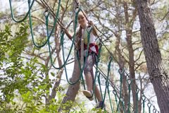 Adolescente de la muchacha con el equipo que sube en un parque de atracciones de la cuerda Foto de archivo libre de regalías