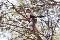 Adolescente de la muchacha con el equipo que sube en un parque de atracciones de la cuerda Imagen de archivo libre de regalías