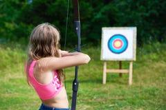 Adolescente de la muchacha con el nock y los objetivos del arco a la blanco Foto de archivo