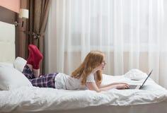Adolescente de la muchacha con el ordenador portátil en cama Fotografía de archivo