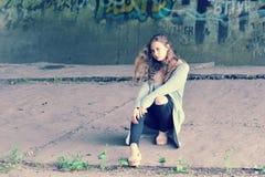 Adolescente de la muchacha con el pelo marrón que fluye que se sienta contra w concreto Fotos de archivo