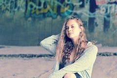 Adolescente de la muchacha con el pelo marrón que fluye que se sienta contra w concreto Imagen de archivo