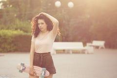 Adolescente de la muchacha con el pelo rizado y el monopatín Fotos de archivo libres de regalías