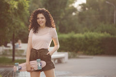 Adolescente de la muchacha con el pelo rizado y el monopatín Foto de archivo