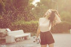 Adolescente de la muchacha con el pelo rizado y el monopatín Imagenes de archivo