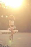 Adolescente de la muchacha con el pelo rizado y el monopatín Imagen de archivo