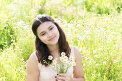 Adolescente de la muchacha con el ramo de margaritas en prado del verano Imagen de archivo