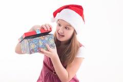 Adolescente de la muchacha con un regalo en un sombrero de Papá Noel Imagen de archivo