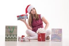 Adolescente de la muchacha con un regalo en un sombrero de Papá Noel Imágenes de archivo libres de regalías