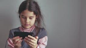 Adolescente de la muchacha en auriculares con su forma de vida interior del smartphone Foto de archivo libre de regalías