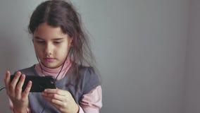Adolescente de la muchacha en auriculares con su forma de vida interior del smartphone Foto de archivo