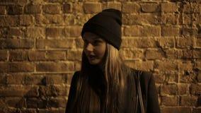 Adolescente de la muchacha en la calle en el café de consumición y esperar de la noche almacen de metraje de vídeo