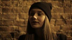 Adolescente de la muchacha en la calle en el café de consumición y esperar de la noche almacen de video