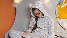 Adolescente de la muchacha en pijamas calientes en rotura de la Navidad que lee un libro que se sienta en la cama almacen de video