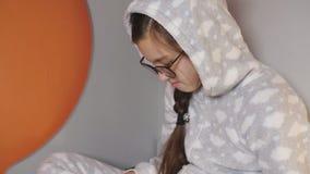 Adolescente de la muchacha en pijamas calientes en rotura de la Navidad que lee un libro que se sienta en la cama, primer almacen de video